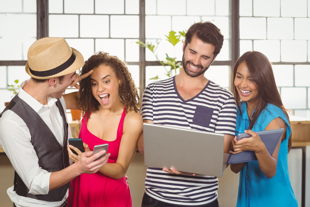 Laughing friends using different types of multimedia at coffee shop